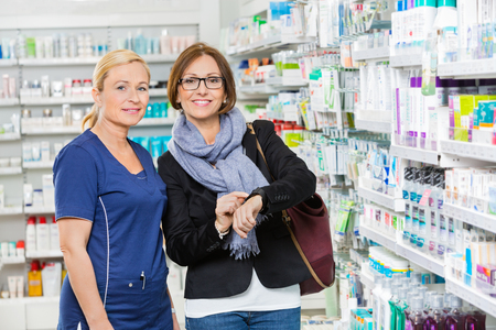 medicine: Portrait of mid adult female customer showing medicine information to pharmacist on smartwatch in pharmacy Stock Photo