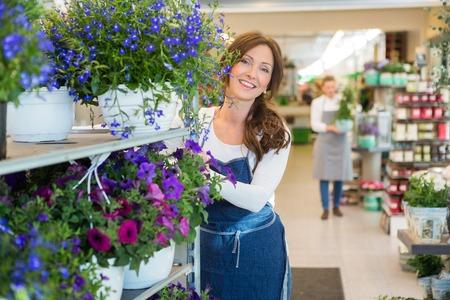 Ritratto di sorridere metà degli adulti fiorista spingendo mensole di fiori in negozio