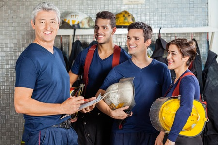 superior: Portrait of happy fireman standing with team at fire station