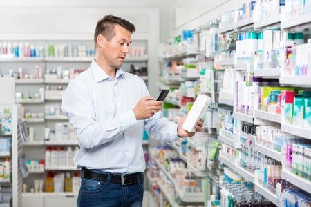 adult male: Mid adult male customer scanning product through mobile phone in pharmacy