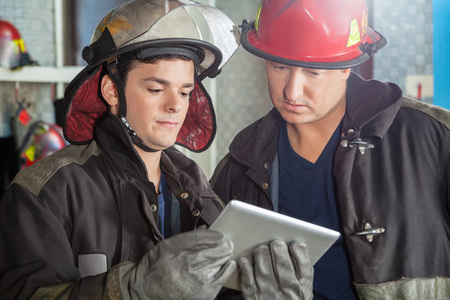 using tablet: Young and mature firemen using tablet computer at fire station Stock Photo