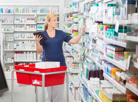 farmacia: Femenina actualización del farmacéutico Stock madura en tableta digital en la farmacia