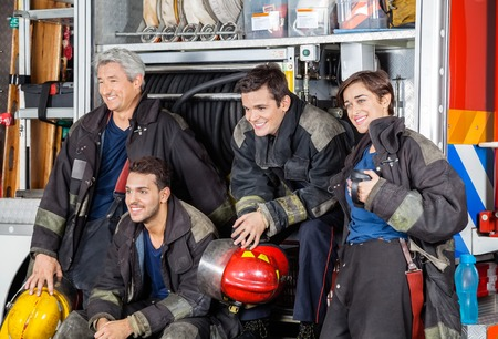first responder: Team of happy firefighters looking away by firetruck at station Stock Photo