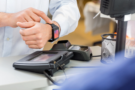 retail: Closeup of male customer paying through smartwatch at counter in pharmacy