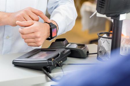 farmacia: Primer plano de cliente masculino pagar a trav�s SmartWatch en el contador en la farmacia