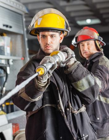 bombero: Los bomberos de sexo masculino confidente de pulverizaci�n de agua durante el entrenamiento en la estaci�n de bomberos Foto de archivo