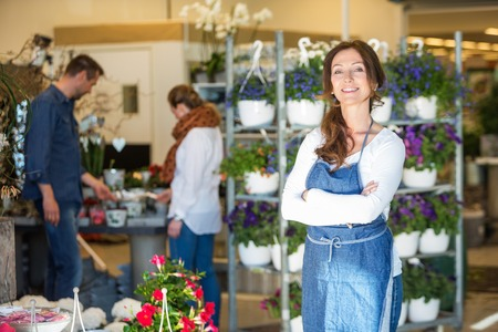 woman shop: Portrait of smiling mid adult female owner with customers in background at flower shop