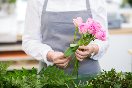 midsection: Midsection of florist making bouquet of roses in flower shop Stock Photo