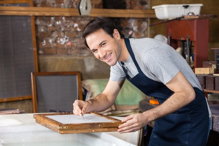 Portrait of confident mid adult male worker using tweezers to clean paper in factory Stock Photo