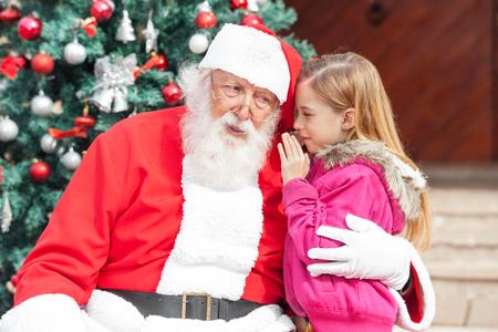 papa noel: Muchacha que dice deseo al oído de Santa Claus contra el árbol de Navidad