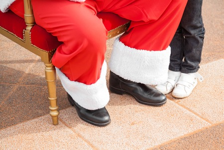 st nicholas: Low section of Santa Claus and girl outdoors