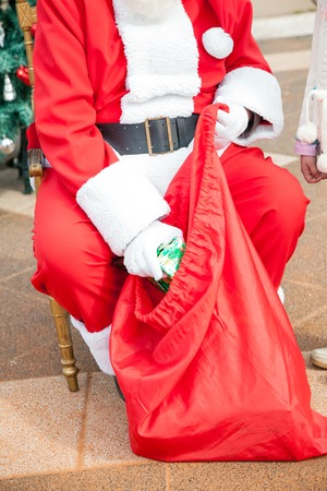 santaclaus: Low section of Santa Claus taking out gift from bag outdoors