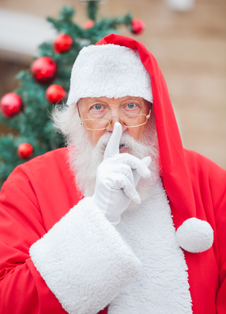 sh: Portrait of Santa Claus with finger on lips outdoors