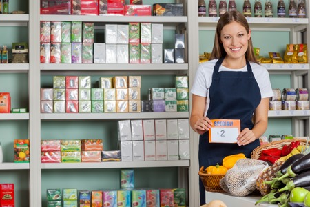 grocery shelves: Portrait of confident saleswoman displaying pricetag in grocery store