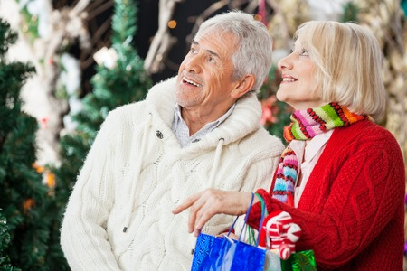 shoppingbag: Happy senior couple with shopping bags looking up at Christmas store
