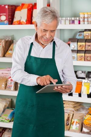 Gelukkig senior mannelijke eigenaar met behulp van digitale tablet in supermarkt