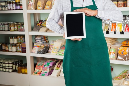 business products: Midsection of male owner showing digital tablet in grocery store Stock Photo