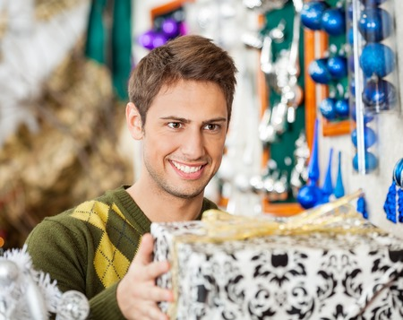 sueteres: Handsome young man holding Christmas present in store