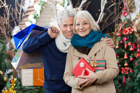 shoppingbag: Portrait of happy senior couple with shopping bags and presents standing at Christmas store