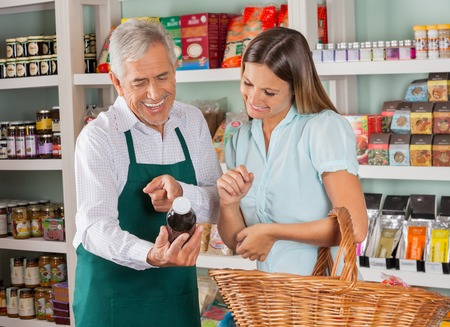 Vendedor mayor que asiste al cliente femenino en comestibles de las compras en la tienda