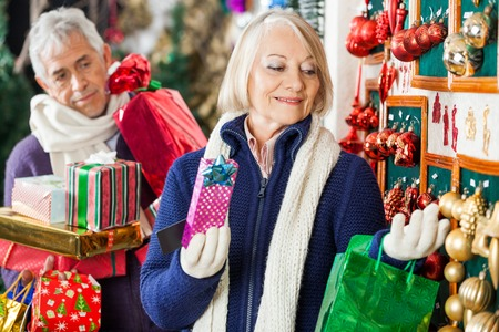shoppingbag: Senior woman selecting Christmas ornaments at store with man holding presents in background
