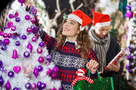 fake christmas tree: Happy young woman shopping for Christmas decorations with man in store