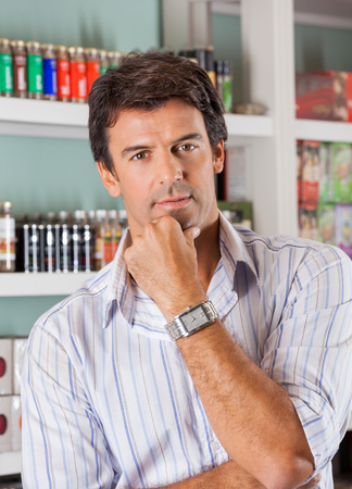 Portrait of handsome mid adult man with hand on chin in supermarket