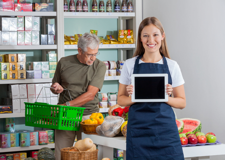 saleswoman: Portrait of saleswoman showing digital tablet while senior man shopping in background