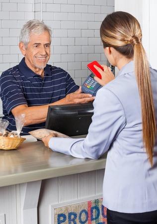Anziano holding del commesso lettore elettronico mentre il cliente femminile pagare attraverso il cellulare photo
