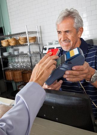 Anziano holding del commesso lettore elettronico mentre cliente pagante attraverso smartphone photo
