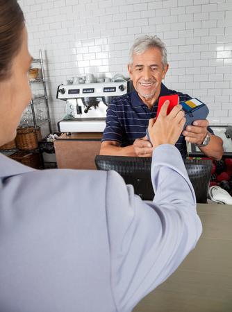 Anziano holding del commesso lettore elettronico mentre femmina cliente effettua il pagamento con cellulare photo