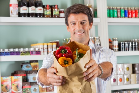 Portrait of happy man showing fresh bellpeppers in paper bag at grocery store photo