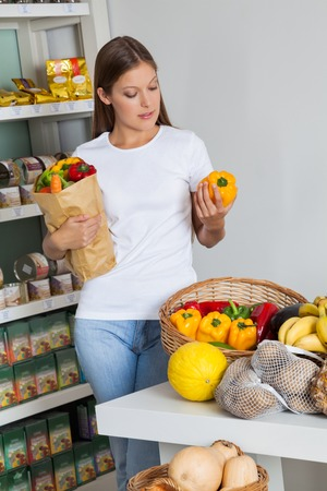 woman bag: Young woman shopping bellpeppers in supermarket