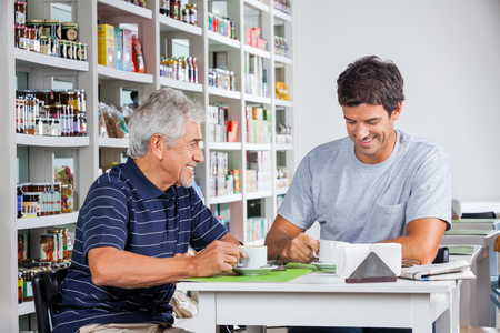 Happy father and son having coffee at table in grocery store photo