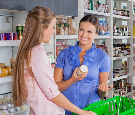 Happy female friends shopping grocery at supermarket photo