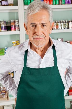 Ritratto di fiducia anziano proprietario maschile in piedi nel negozio di alimentari photo
