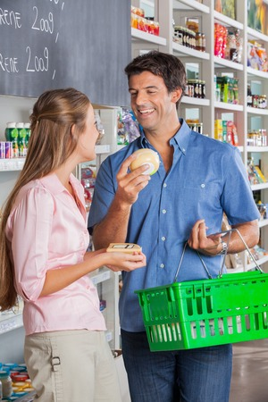 Happy couple comparing cheese at grocery store photo