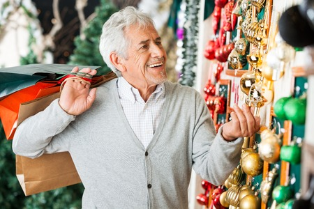 shoppingbag: Happy senior man with shopping bags buying Christmas ornaments at store