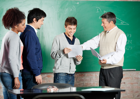 pass test: Happy male professor giving exam result to student with classmates standing in a row at classroom Stock Photo
