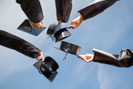 graduacion de universidad: Directamente debajo del tiro de los estudiantes que crían juntas de mortero contra el cielo el día de graduación Foto de archivo