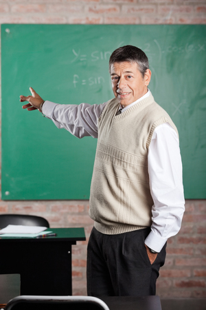 greenboard: Portrait of confident male teacher with hand in pocket pointing towards greenboard at classroom Stock Photo