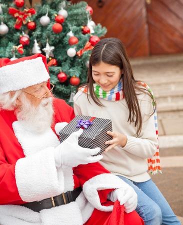 Ragazza che cattura il regalo di Natale da Santa Claus fuori casa photo