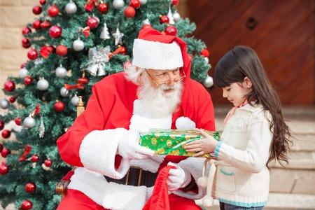 Vista laterale della ragazza prendendo dono da Babbo Natale contro l'albero di Natale photo