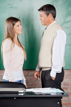 greenboard: Side view of young college student and teacher looking at each other against greenboard in classroom