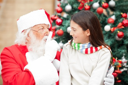 shush: Santa Claus gesturing finger on lips at girl in front of Christmas tree