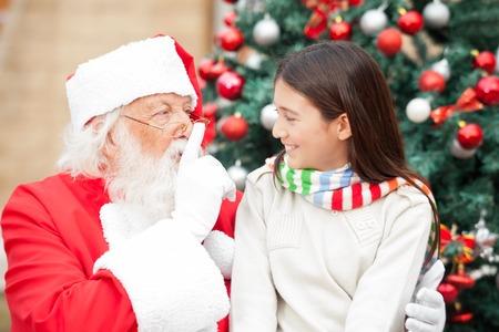 silencio: Santa Claus haciendo un gesto dedo en los labios en la chica delante de árbol de Navidad