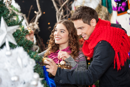winter holiday: Happy young couple shopping for Christmas tree in store Stock Photo
