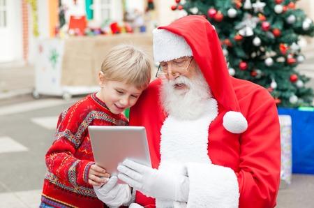 Babbo Natale e il ragazzo con tavoletta digitale insieme in cortile photo