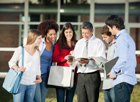 profesor: Profesor de sexo masculino feliz que explica la lecci�n a los estudiantes en el campus universitario