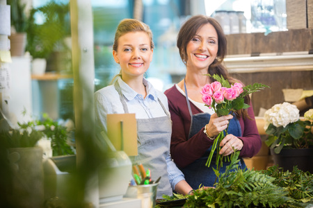 arranging: Portrait of happy florists making bouquet of pink roses in flower shop